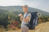 Elderly hiker holding a pair of binoculars and looking away outdoors poster