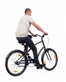 back view of a man with a bicycle. cyclist rides a bicycle. Rear view people collection.  backside v poster