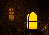 Garden Light With Cross On It Reflecting Against A Marble Tile Wall. An Outdoor Yellow And Orange Gl poster