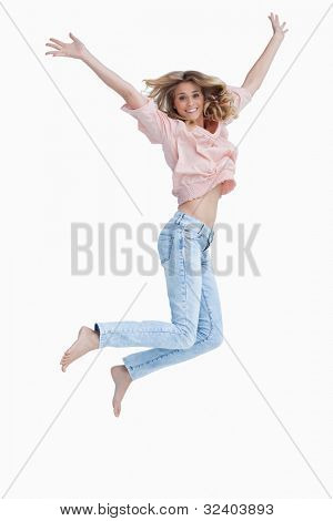 A woman is jumping up in excitement with her arms raised against a white background