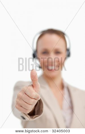 Thumbs up of a businesswoman wearing a headset against white background