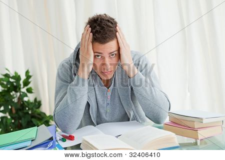 Portrait of a distressed student doing his homework while holding his head
