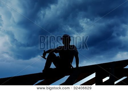 Builder Or Carpenter Resting On Top Of Roof Structure