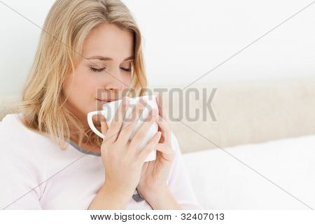 A woman with her eyes closed, in bed with a cup raised to her nose to take in the smell of the cups aroma.