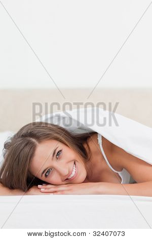 A close up shot of a smiling woman as she looks straight ahead and resting her head upon her hands.
