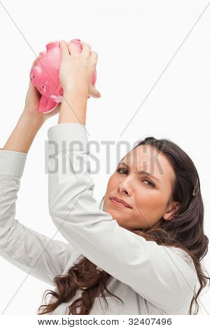 Portrait of a brunette holding an empty piggy bank against white background