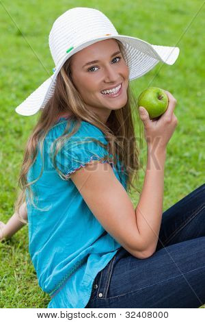 Attractive young girl sitting on the grass while eating a green apple