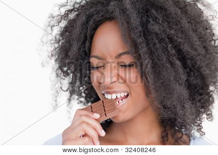 Young woman closing her eyes while eating chocolate against a white background
