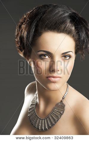 Das Mädchen mit Halskette, sie sieht der Linse