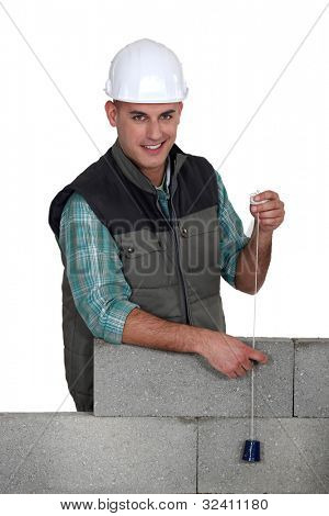 Tradesman holding a plumbline