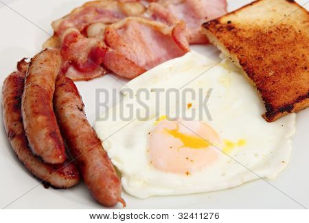 Traditional, unhealthy, English cooked breakfast of fried bacon, egg, chipolata sausages and bread