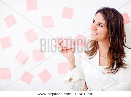 Multitask business woman with post-its and smiling