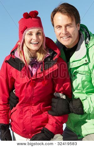 Couple Standing In Snow Wearing Warm Clothes On Ski Holiday In Mountains