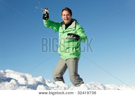 Man About To Throw Snowball Wearing Warm Clothes On Ski Holiday In Mountains