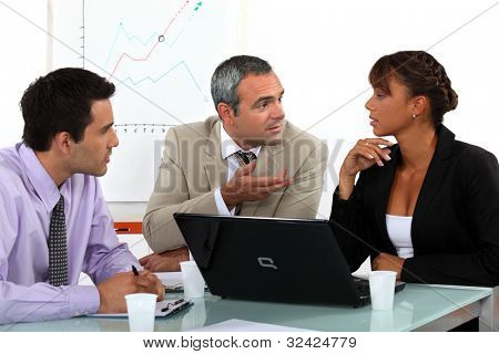 Three people in animated business meeting