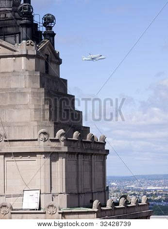 NEW YORK - Oct 8: The space shuttle Enterprise mounted on NASA's 747 Shuttle Carrier Aircraft flies north along the Hudson River with the Standard Oil Bldg in the foreground on October 8, 2011 in NYC.