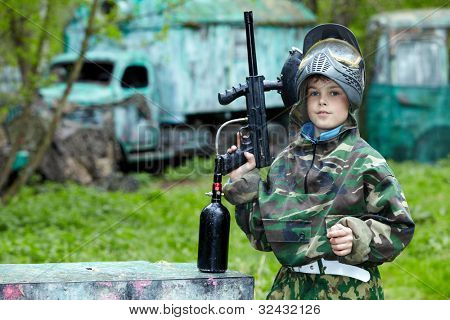 Boy in the camouflage suit holds a paintball gun barrel up, standing on the paintball ground with old lorry and bus on the background.