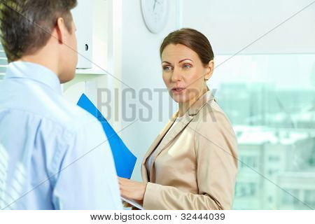 Business woman looking at his male colleague questioningly or in annoyance