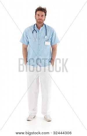 Handsome young doctor standing with hands in pocket, smiling.
