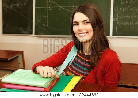 beautiful teen girl high achiever in classroom over desk happy smiling