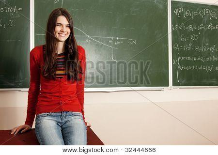 beautiful teen girl high achiever in classroom near desk happy smiling