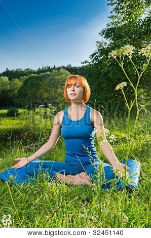 Red woman practicing fitness yoga outdoors