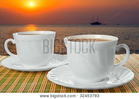 Two White Cups With Saucer On Background Of Sunset.