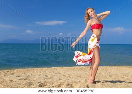 Pretty blonde girl wearing a bikini in a happy mood at the beach