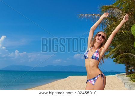 Attractive young woman in sunglasses joyfully raising her arms in celebration of the freedom of a beach vacation