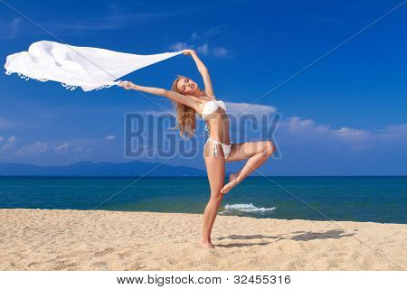 Bikini clad blonde beauty in a dancers pose on soft white sand with the ocean in the background