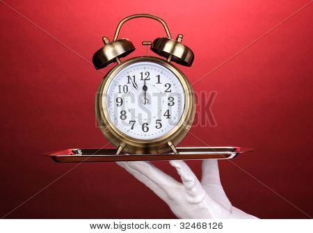 De la mano en el guante con bandeja de plata con despertador sobre fondo rojo