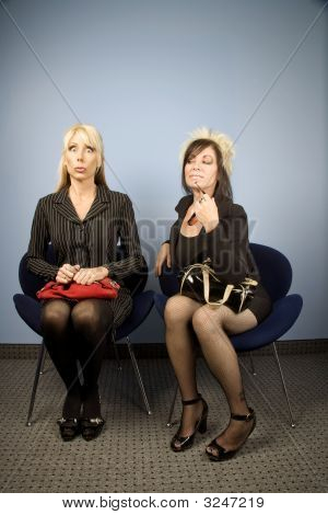 Nervous Businesswoman Seated Next To A Bold Woman