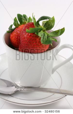 Fresh Red Strawberries inside a White Teacup with Plain White Ba