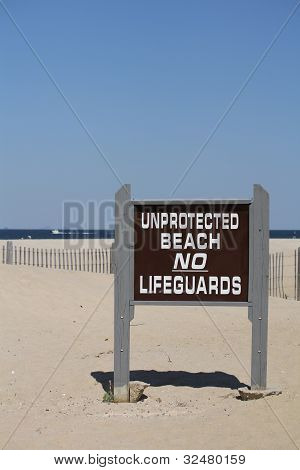 Brown Sign on Beach - Unprotected Beach No Lifeguards