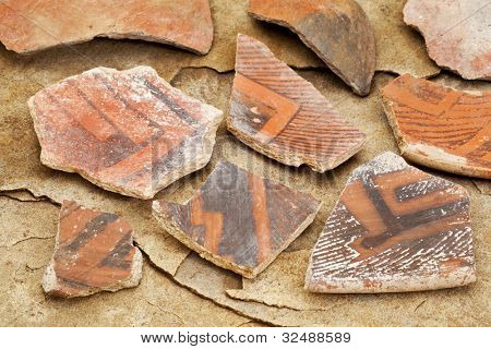 Arizona Anasazi pottery shards, ancient Native American Indian artifacts, several fragments of a bowl,  on a sandstone background