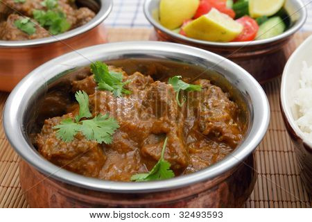 A bowl of Madras butter beef curry with rice, salad and another curry bowl in the background