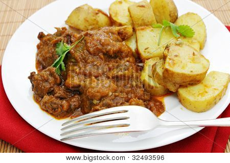 A madras butter beef curry served with curried potatoes and garnished with coriander leaves