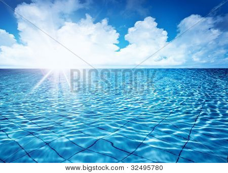 Endless pool water with blue sky background and bright sun light, fresh natural landscape, rippled texture and pattern, swimming pool seamless surface, summer travel vacation and spa leisure concept