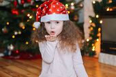 Happy Little Girl Under Christmas Tree And Fireplace At Home. Kids Play Near Christmas Tree. Family  poster