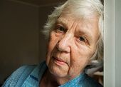 Elderly old gray-haired sad woman face close-up portrait poster