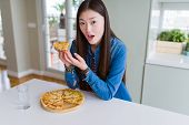 Beautiful Asian woman eating a slice of cheese pizza scared in shock with a surprise face, afraid an poster