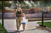 Young Mother With Her Daughter In Hot Weather, Cool Off At The Gates Of Climate Control In The Water poster