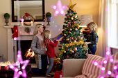 Side view of a young Caucasian woman and her young son and daughter decorating the Christmas tree in poster
