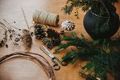 Making Christmas Wreath.fir Branches, Pine Cones, Thread, Scissors, Wooden Circle, Berries And Herbs poster