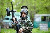 stock photo of bus-shelter  - Boy in the camouflage holds a paintball gun barrel up and says something - JPG
