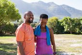 Cheerful black couple resting together after jogging in the park. Happy mature man and woman laughin poster