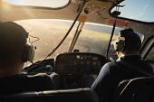Scene Of Soft Blurry Helicopter Cockpit From The Rear Side Which Have Two Pilots At The Front Seat W poster