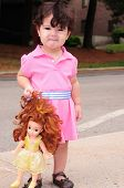 Image of little girl in a pink dress holding her doll.