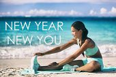 New Year new you motivational quote message on beach background. Asian woman training stretching on  poster