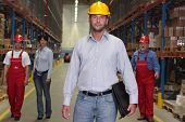 Boss With Briefcase At The Front Of Workforce In Warehouse